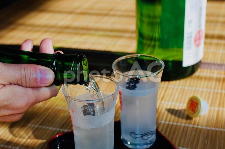 一升瓶からグラスに注がれるお酒の写真