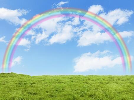 Meadows, blue sky and rainbow