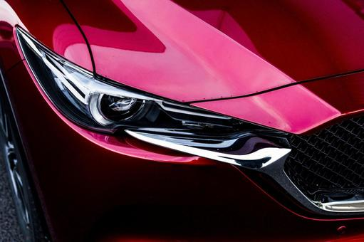 Automotive headlight picture (MAZDA New CX - 5). An image impressive with a deep red color that drifts a sense of quality.