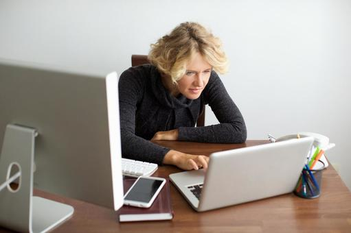Working mother 9 sandwiched between desktop computer and laptop computer 9