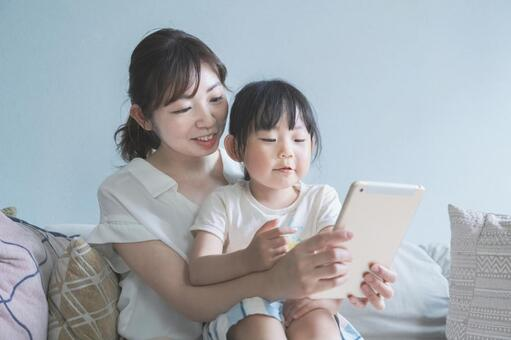 소파에 앉아 온라인 커뮤니케이션을하는 부모와 자식
