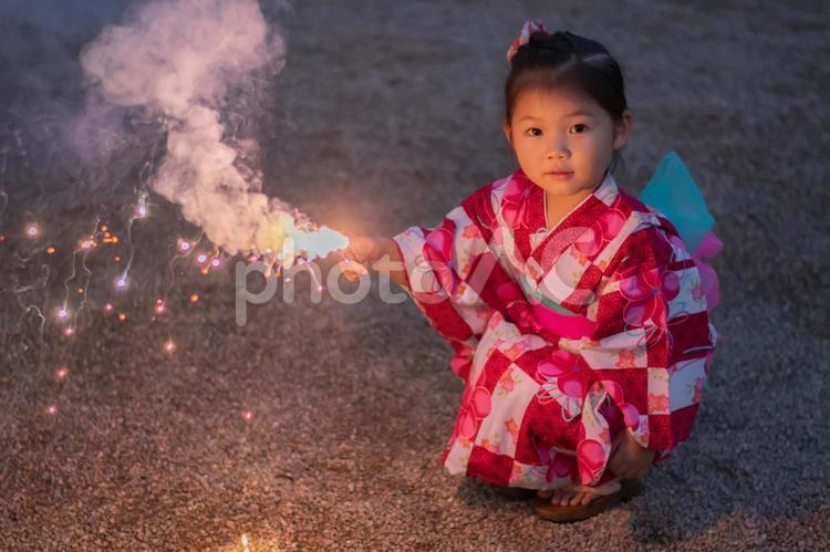 A Japanese girl wearing red, pink and white patterned Yukata, holding a sparklers