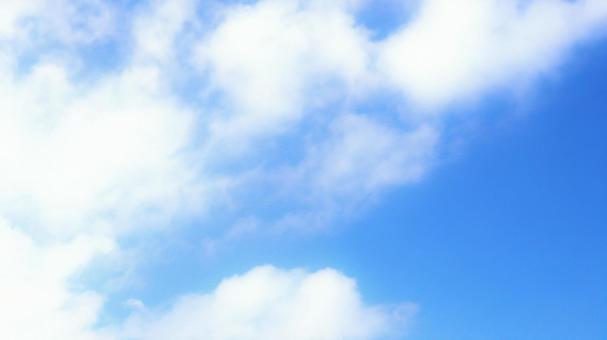 Background material of the sky where fluffy clouds float in the blue sky