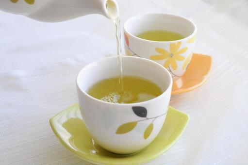 Pour green tea into a teacup with a kyusu_hot drink