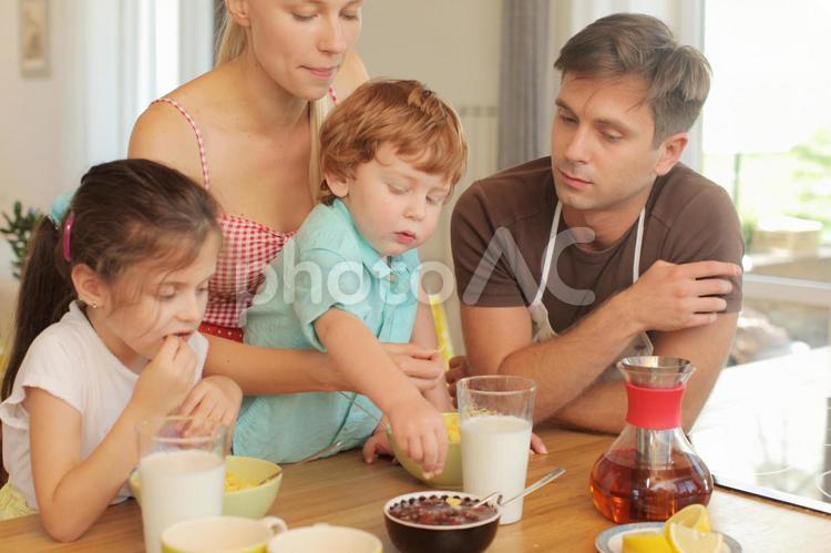 コーンフレークを食べる子供たちと見守る両親1の写真