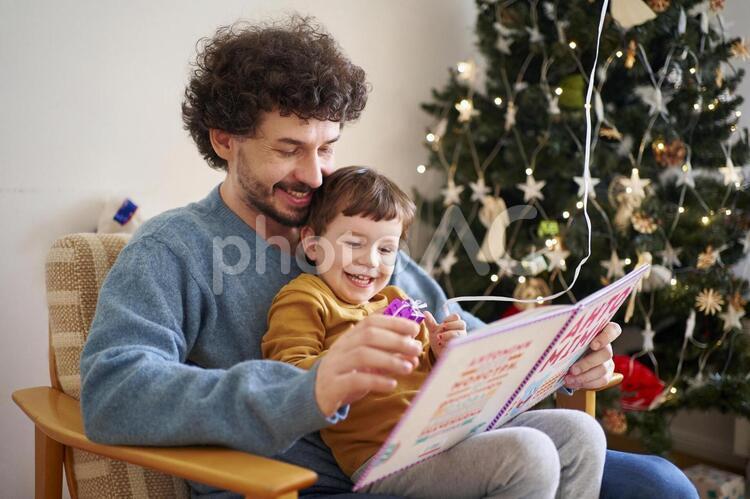 クリスマスの家族 絵本を読む親子の写真