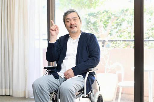 A smiling senior man in a wheelchair with his index finger