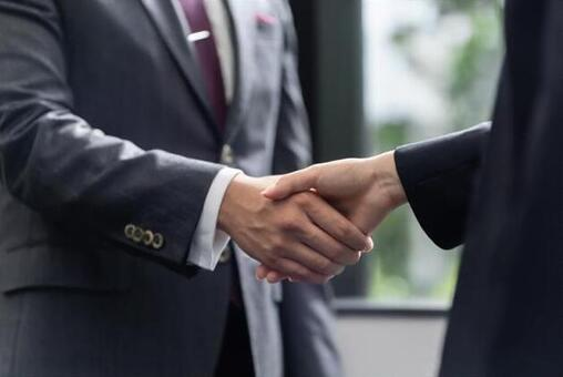 Shaking hands between a male businessman and a female business woman