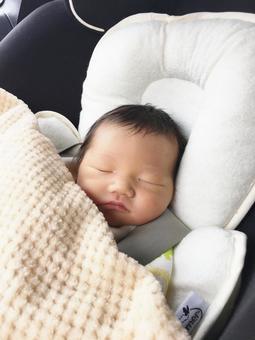 A newborn sleeping in a child seat