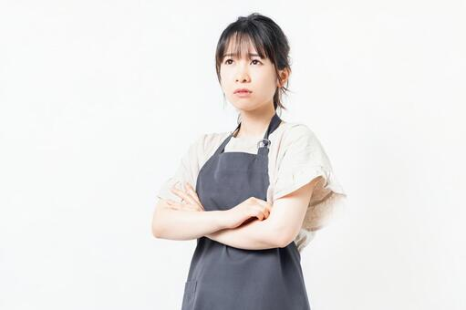 A young woman wearing an apron with her arms crossed