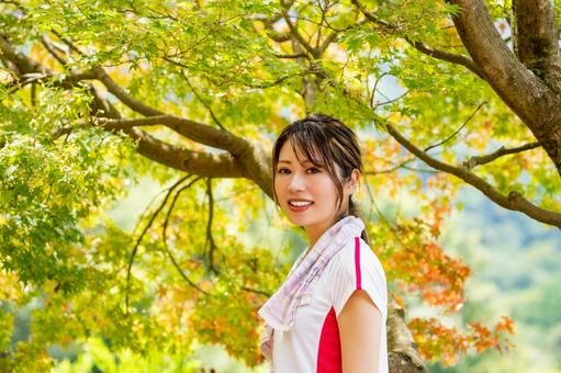 A smiling woman against the backdrop of autumn leaves