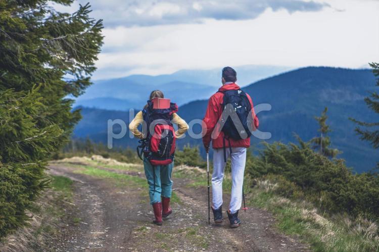 山道を歩くトレッカーのカップル11の写真