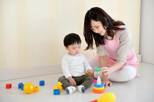 玩具で遊ぶ保育士と子供