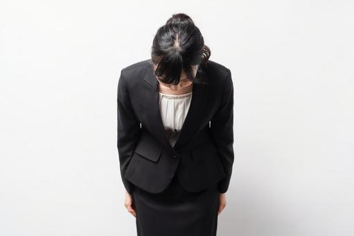 Business woman standing in front of a white background and apologizing