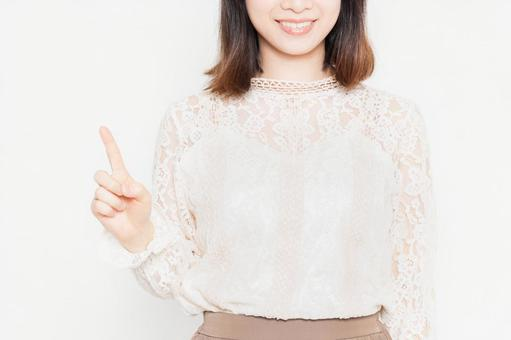 A young woman in a lace blouse standing in front of a white background and showing points