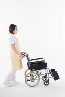 A woman pushing a wheelchair 1