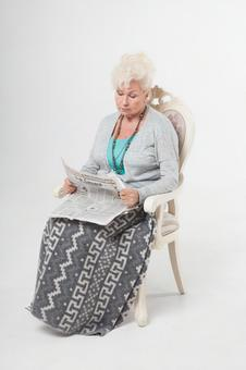 Sitting in a chair and reading a newspaper Foreigner elderly female 1