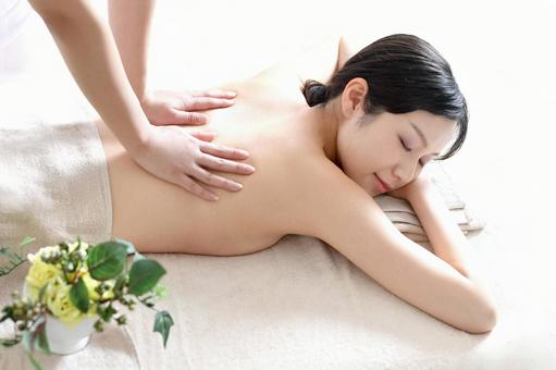 Young woman undergoing esthetic treatment in a massage bed