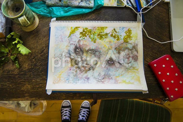 木の机で水彩画を描く_自分の足の写真