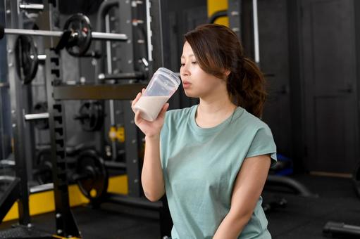 Woman drinking protein in the gym