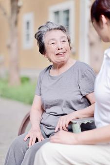 屋外で話をするおばあちゃんと介護士