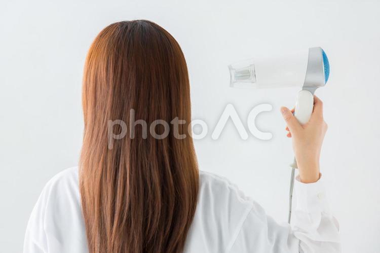 ドライヤーをかける女性の写真