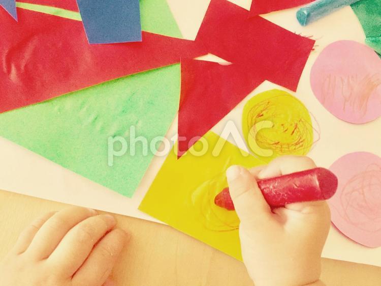 折り紙のはり絵とクレヨンで遊ぶこどもの手の写真