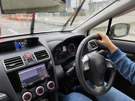 Female driver commuting by car on a rainy day