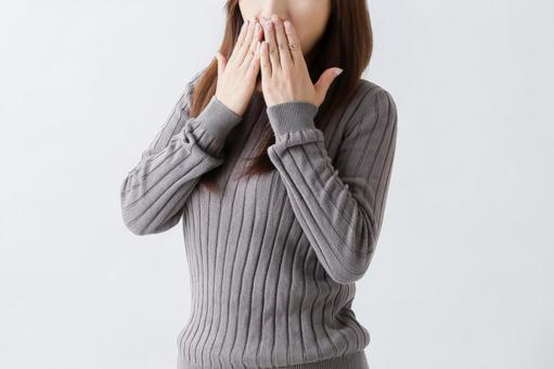 Woman putting her hand on her mouth
