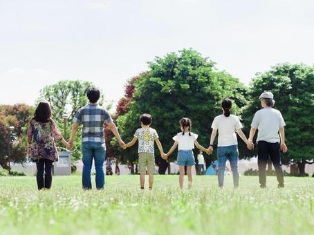 A three-generation family holding hands in a sunny park