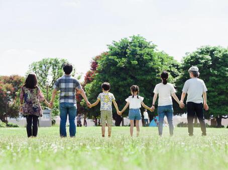 一個三代家庭,手牽著手在一個陽光明媚的公園
