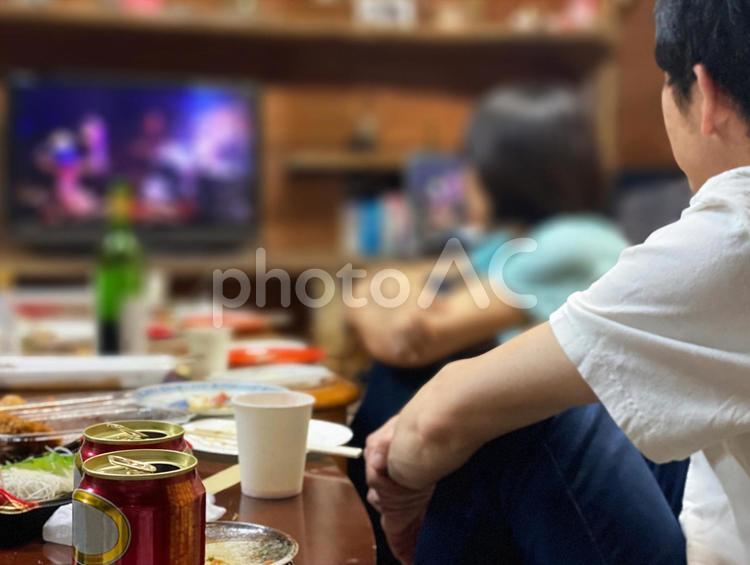 食事しながらテレビでライブを見る家族の写真
