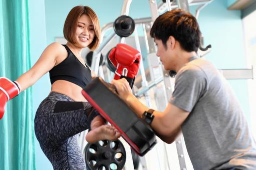 Female and male trainers kicking mitts