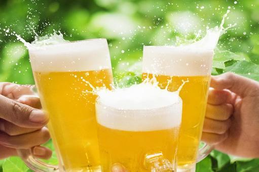 生ビールで乾杯_しぶき_新緑ヘデラ背景