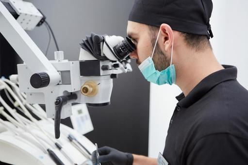 Male dentist treating with microscope 15