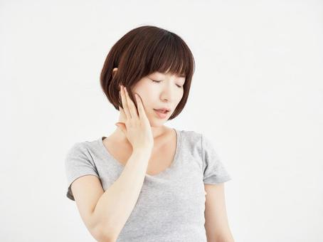 A woman holding a painful jaw on a white background
