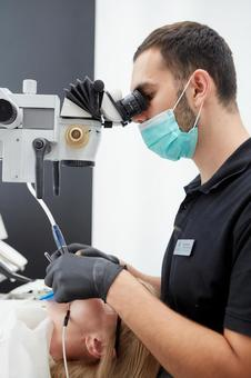 Male dentist treating with a microscope 12