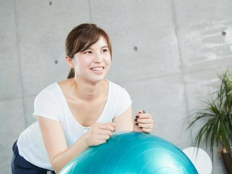 A Japanese woman doing a plank with a balance ball