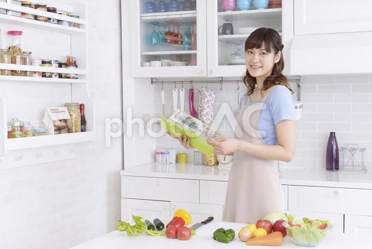 キッチンでレシピを見る女性3の写真