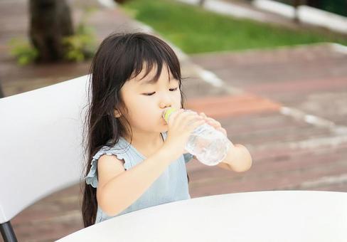 女孩用塑料瓶喝水