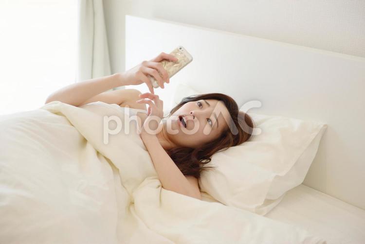 横になってスマホを見る女性8の写真
