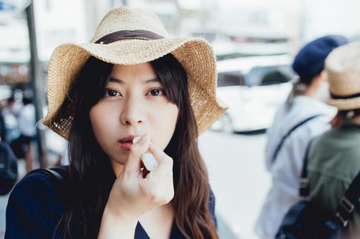 Woman in straw hat applying lip balm