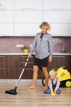 Working mother with a son and a vacuum cleaner that imitates cleaning 11