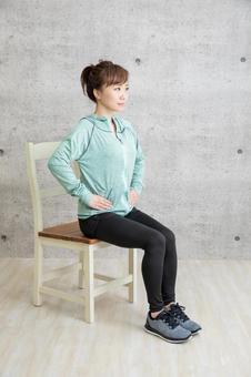 A woman training using a chair