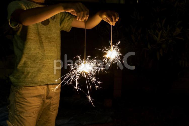 両手に線香花火を持つの写真