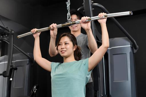 Asian women doing lat pull-down and male trainers assisting