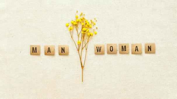 Male and female English letters and yellow gypsophila placed on canvas