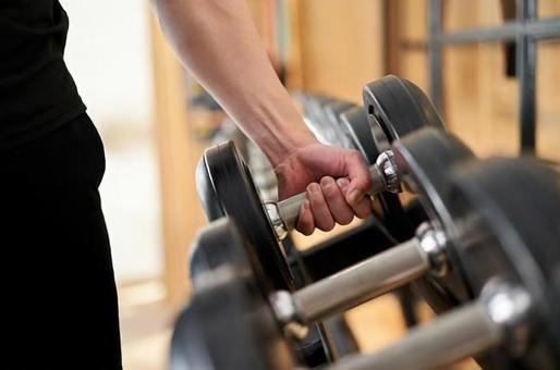 Hands of an Asian man taking dumbbells from a rack