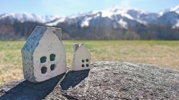Two small house with snow mountain and grass and rocks
