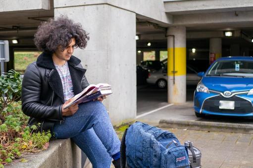 돌계단에 앉아 책을 읽는 남자 대학생